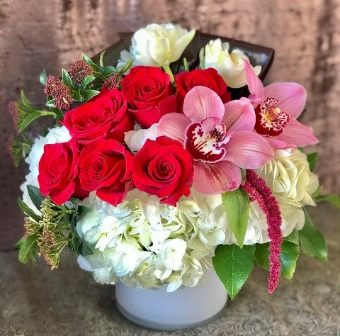 Red Roses, Pink Orchids, White Tulips arranged in a white glass vase.
