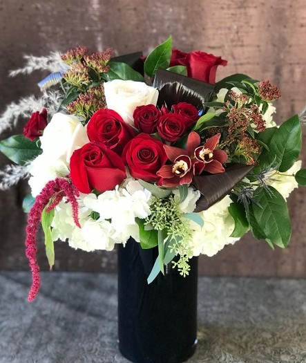 Red roses in large 10 inch tall black glass vase, full of lots of beautiful textures.